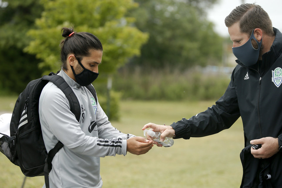 Photo - Jose Hernandez with OKC Energy FC gets hand sanitizer from Cody Legg as he arrives for soccer practice in Oklahoma City, Wednesday, May 13, 2020. [Bryan Terry/The Oklahoman]
