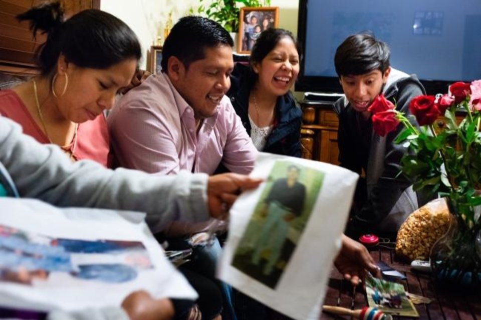 Photo -  Romero León brought a stack of photos to share with her family: daughter Guillermina Sánchez, son-in-law Abdias Guardian, and grandchildren Chelsy Guardian and Oswaldo Guardian. [Sarah L. Voisin/The Washington Post]