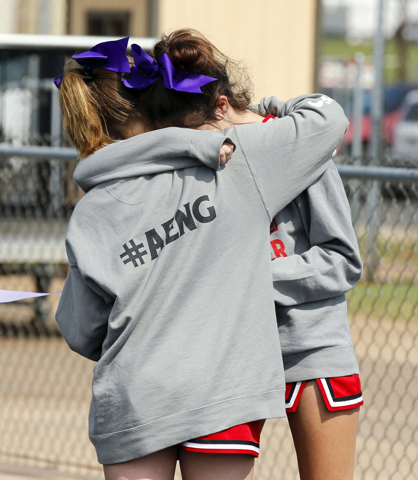 Photo - McLoud cheerleaders hug before a high school football game between McLoud and Cushing at O'Dell Field in Cushing, Okla., Saturday, Oct. 6, 2018. The game was postponed and moved from McLoud after Kaylen Thomas, a McLoud High School student, was fatally shot the previous day. Photo by Nate Billings, The Oklahoman