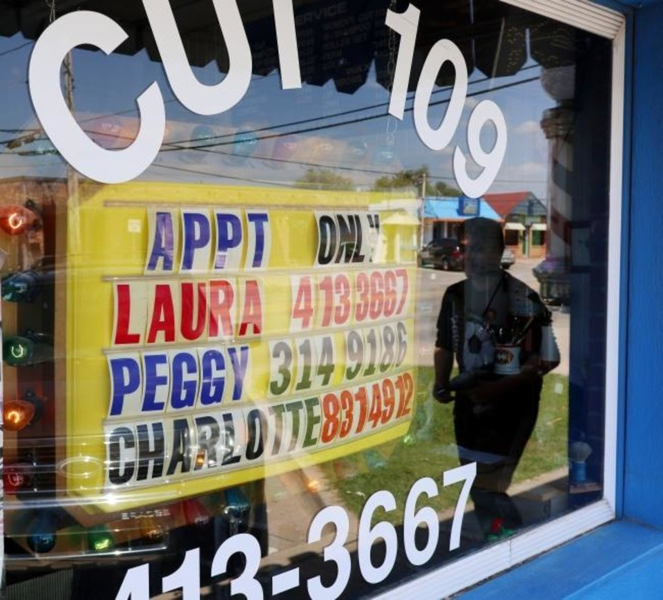 Photo -  A sign in the window at Cut 109 in Moore lets people know they can schedule appointments on Monday.  [Doug Hoke/The Oklahoman]