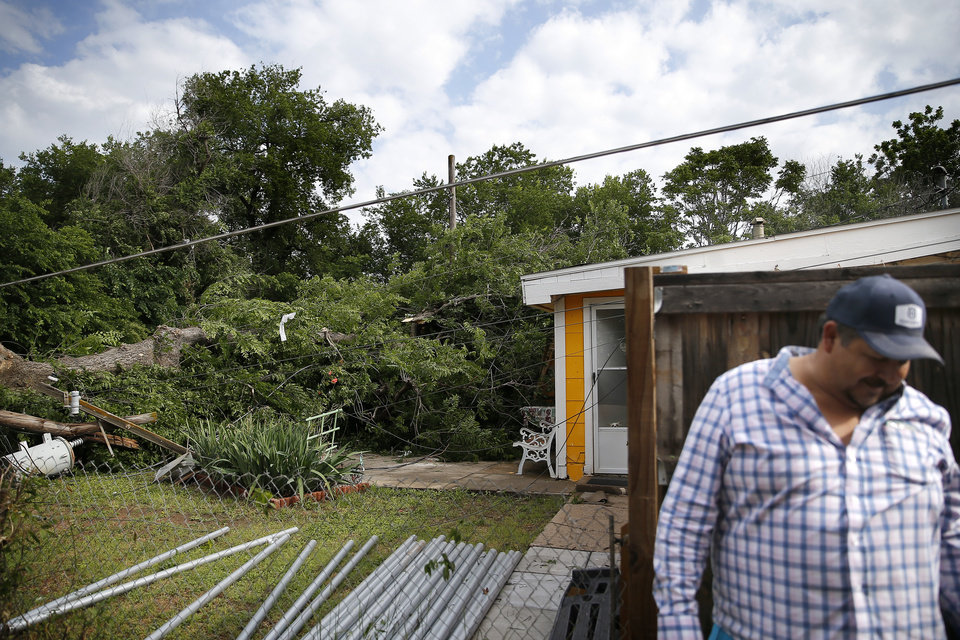 Photo - Juan Luna walks away from his backyard at his home near 21st and McKinley after an apparent tornado moved through the area in Oklahoma City, Sunday, May 26, 2019. Luna said the sirens sounded and it instantly became windy. He stood next to an interior wall with his 12 year old daughter.  [Sarah Phipps/The Oklahoman]