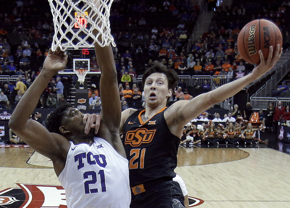 Photo - Oklahoma State's Lindy Waters III, right, puts up a shot under pressure from TCU's Kevin Samuel during the first half of an NCAA college basketball game in the Big 12 men's tournament Wednesday, March 13, 2019, in Kansas City, Mo. (AP Photo/Charlie Riedel)