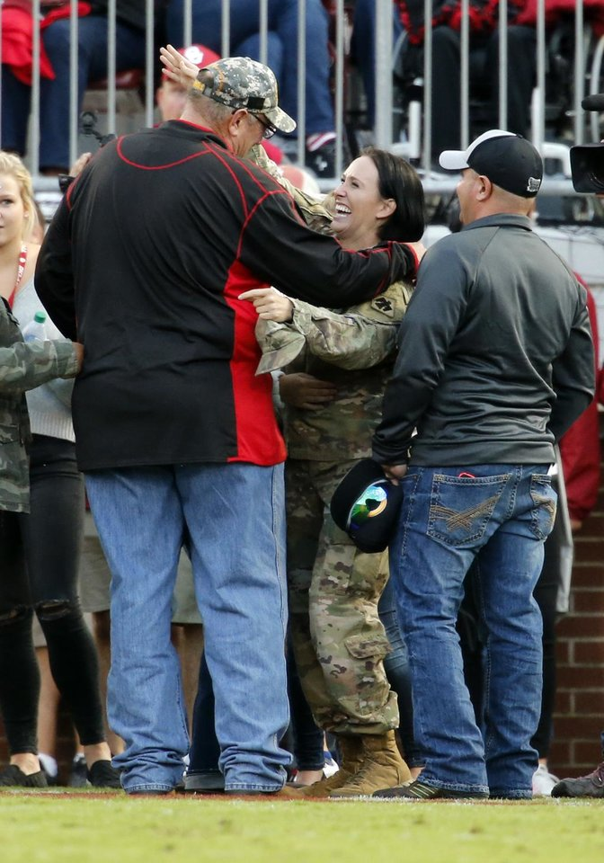 Photo - National Guard member Sgt. Brandy Dill surprises her family in person as she is honored during the first half for her service with a video during a college football game between the University of Oklahoma Sooners (OU) and the Army Black Knights at Gaylord Family-Oklahoma Memorial Stadium in Norman, Okla., on Saturday, Sept. 22, 2018. Photo by Steve Sisney, The Oklahoman