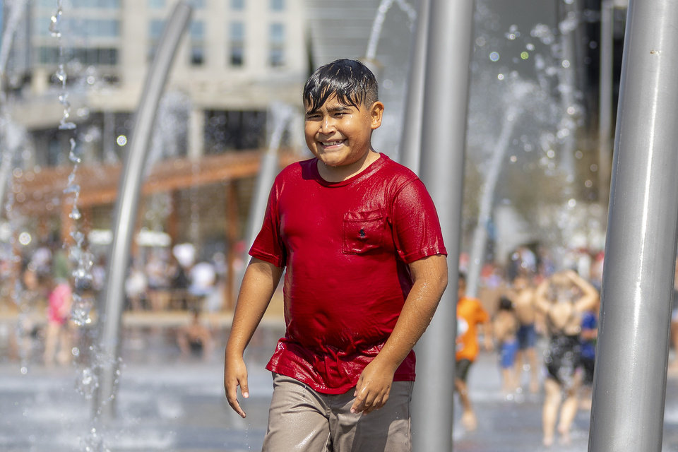 Photo - Joan, age 10, plays in the water at the splash pad during the grand opening weekend of Scissortail Park in Oklahoma City, Sunday, Sept. 29, 2019. (Alonzo Adams for The Oklahoman)