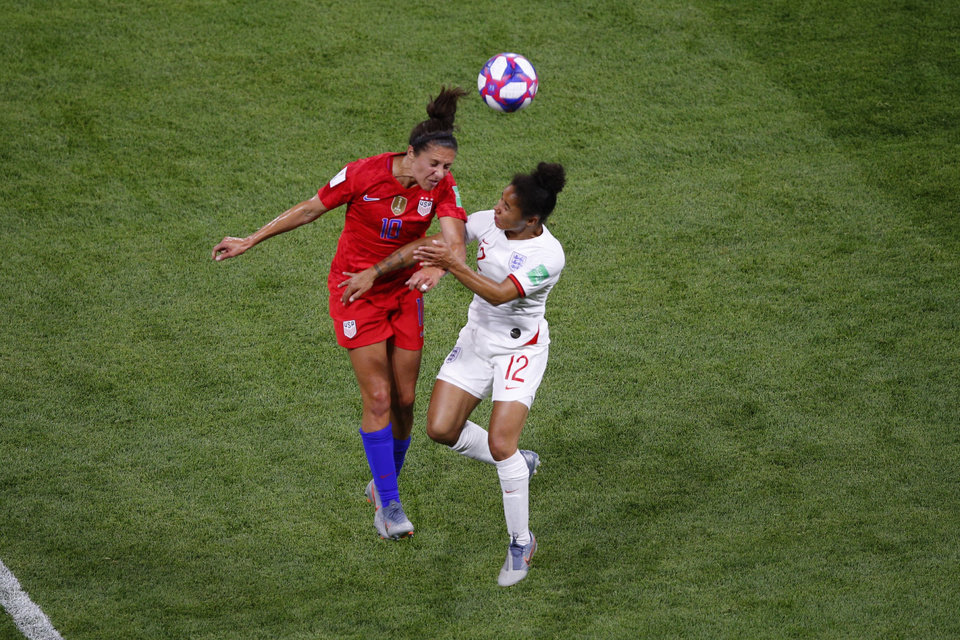 Photo - United States' Carli Lloyd, left, and England's Demi Stokes jump for the ball during the Women's World Cup semifinal soccer match between England and the United States, at the Stade de Lyon outside Lyon, France, Tuesday, July 2, 2019. (AP Photo/Francois Mori)