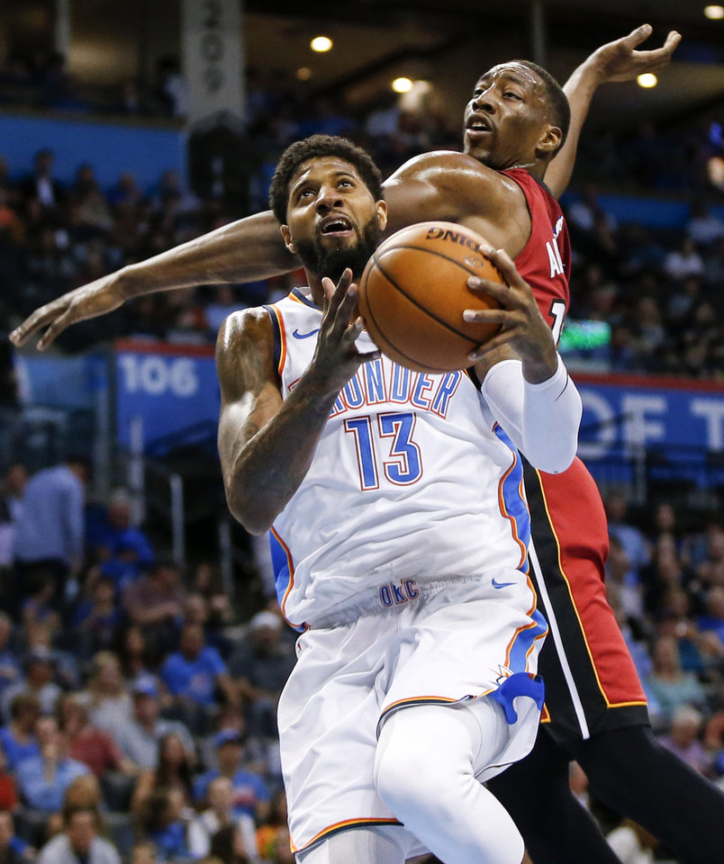 Photo -  Oklahoma City's Paul George (13) tries to score in front of Miami's Bam Adebayo (13) in the first quarter at Chesapeake Energy Arena on March 23. [oklahoman archives]