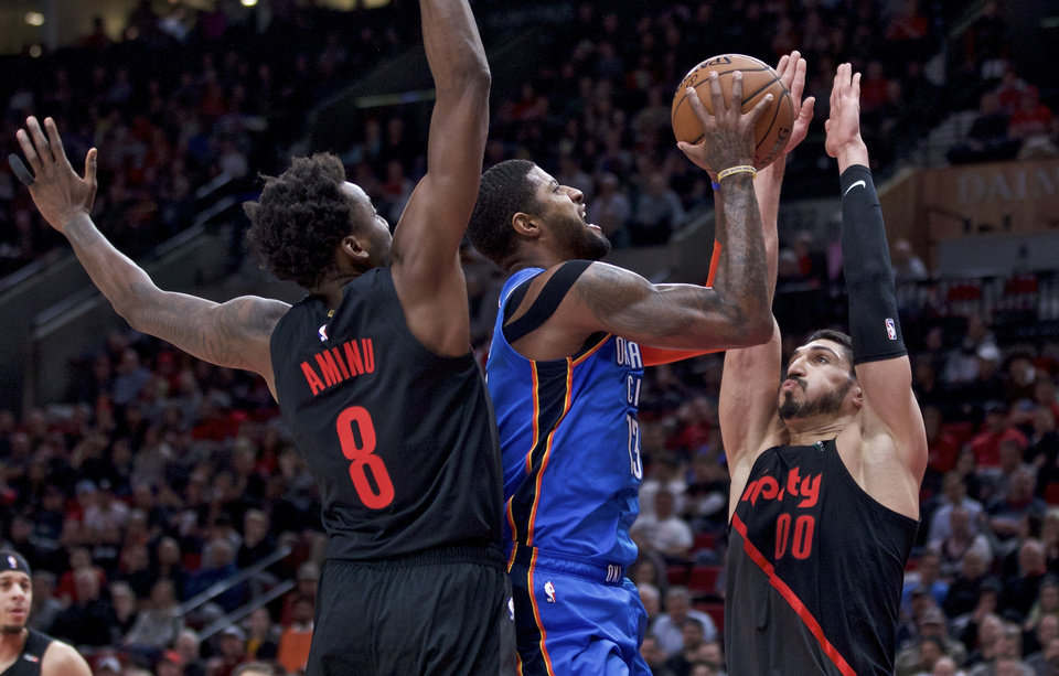 Photo - Oklahoma City Thunder forward Paul George, center, shoots between Portland Trail Blazers center Enes Kanter, right, and forward Al-Farouq Aminu during the first half of an NBA basketball game in Portland, Ore., Thursday, March 7, 2019. (AP Photo/Craig Mitchelldyer)