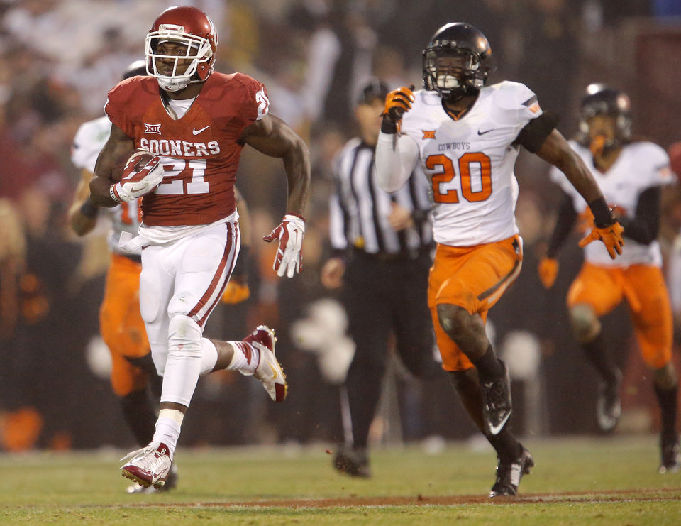Photo - Keith Ford (21) runs past Oklahoma State's Larry Stephens (20) for a long gain in the fourth quarter of a Bedlam college football game between the University of Oklahoma Sooners (OU) and the Oklahoma State Cowboys (OSU) at Gaylord Family-Oklahoma Memorial Stadium in Norman, Okla., Saturday, Dec. 6, 2014. Photo by Bryan Terry, The Oklahoman
