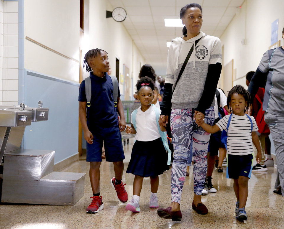 Photo - Loria Phillips walks with her children Jhaidon, 8, in third grade, Rian Phillips, 4, in pre-K and Adrian Phillips, 3, as they look for their classrooms inside Britton Elementary on the first day of school in Oklahoma City, Monday, Aug. 12, 2019. [Bryan Terry/The Oklahoman]