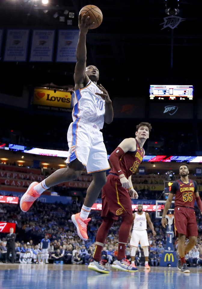 Photo - Oklahoma City's Deonte Burton (30) goes up for a lay up as Cleveland's Cedi Osman (16) looks on during the NBA game between the Oklahoma City Thunder and the Cleveland Cavaliers at the Chesapeake Energy Arena,  Wednesday, Nov. 28, 2018.Photo by Sarah Phipps, The Oklahoman