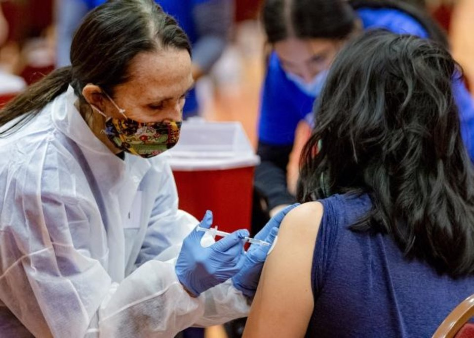 Photo -  Members of IMMY Labs administer inoculations during a Covid-19 vaccination pod at the Embassy Suites by Hilton Norman Hotel & Conference Center in Norman, Okla. on Monday, Feb. 22, 2021.  [Chris Landsberger/The Oklahoman]