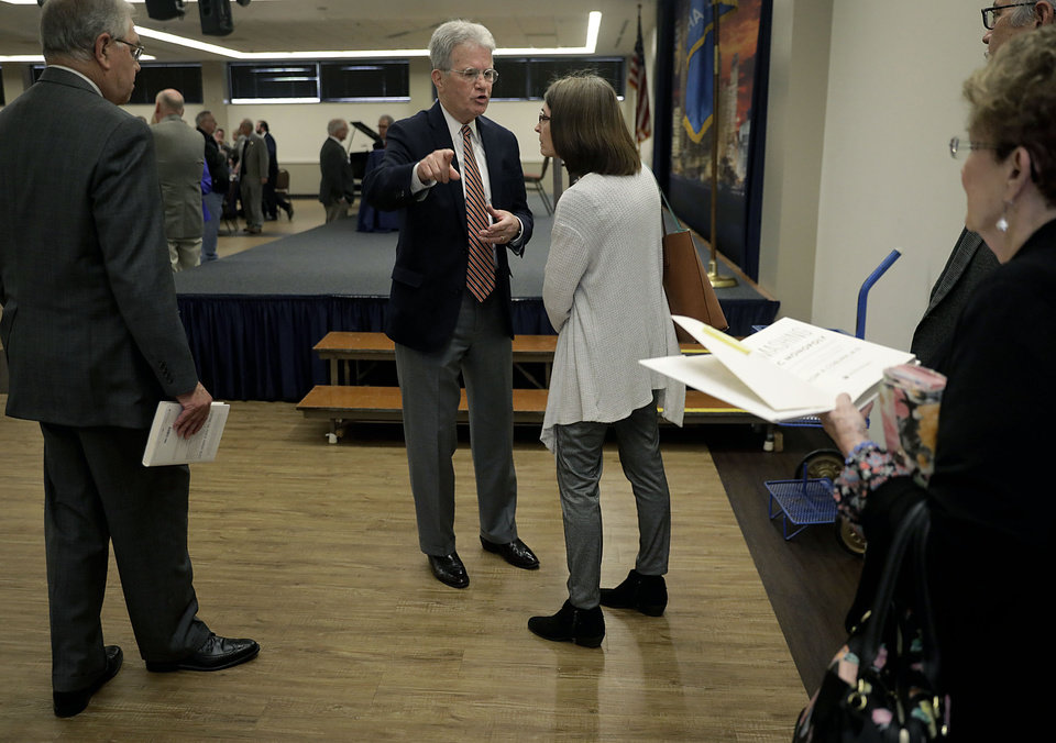 Photo - Former Senator Dr. Tom Coburn speaks with Sapulpa Public Schools teacher Cathy Rains about education funding at the Rotary Club of Tulsa April 25, 2018. Rains was questioning Coburn about his proposals for funding and left the conversation unhappy with the response feeling her questions were unanswered MIKE SIMONS/Tulsa World