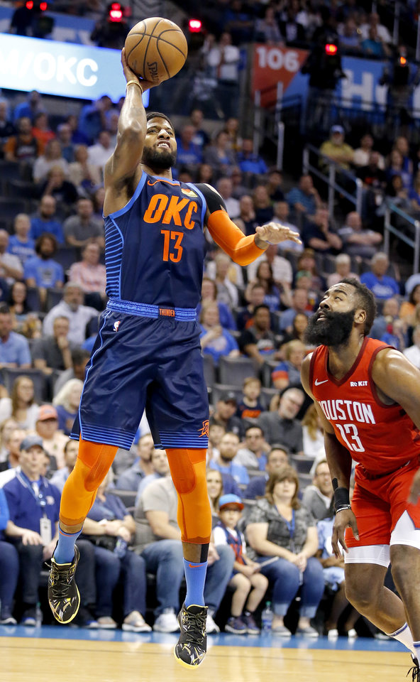 Photo - Oklahoma City's Paul George (13) goes up for a lay up as Houston's James Harden (13) defends during the NBA basketball game between the Oklahoma City Thunder and Houston Rockets at the Chesapeake Energy Arena, Tuesday, April 9, 2019. Cowboys won 6-5. Photo by Sarah Phipps, The Oklahoman