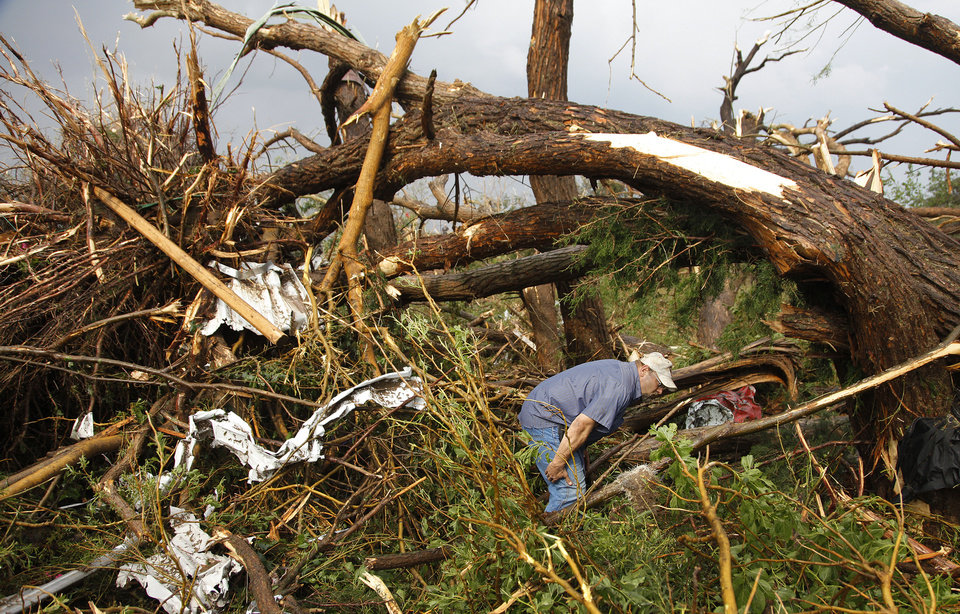 Photo - A passing motorist volunteers his time to the search efforts in a wooded area where two fatalities were confirmed after a tornado swept cars off of I-40 west of El Reno, Tuesday, May 24, 2011. Photo by Chris Landsberger, The Oklahoman