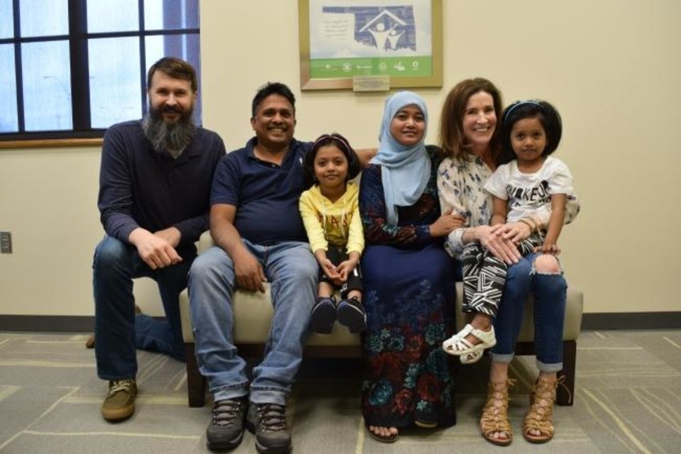 Photo -  Mark Chan, Catholic Charities-OKC's director of refugee resettlement, left, and Temple B'nai Israel member Laura Barlow, right, pose for a picture with members of a refugee family from Myanmar (formerly Burma) who have been adopted by the temple. [Provided]