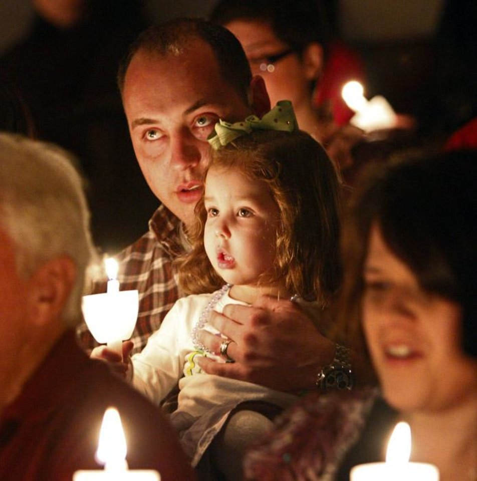 "Photo -  Justin Baylor holds his daughter Brooklynn Baylor, 2, (CQ) as they sing ""Silent Night"" during a Christmas Eve service at Crossings Community Church in Oklahoma City, Friday, Dec. 24, 2010.  Photo by Bryan Terry, The Oklahoman ORG XMIT: KOD"