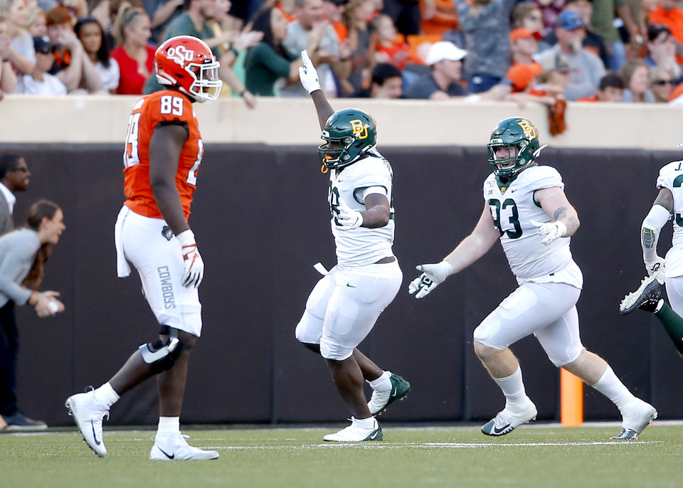 Photo - Baylor's Chidi Ogbonnaya (98) and James Lynch (93) celebrate a Baylor touchdown after recovering a fumble by Oklahoma State's Spencer Sanders (3) as Jelani Woods (89) walks off the field in the fourth quarter during the college football game between Oklahoma State University and Baylor at Boone Pickens Stadium in Stillwater, Okla., Saturday, Oct. 19, 2019. Baylor won 45-27. [Sarah Phipps/The Oklahoman]