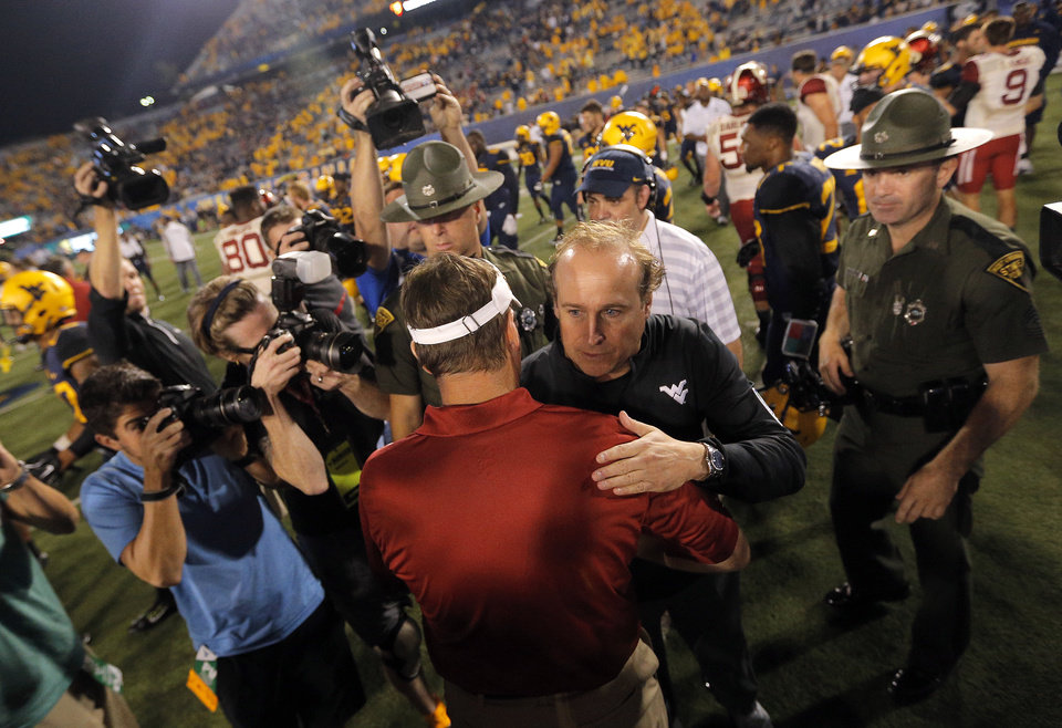 Photo - West Virginia coach Dana Holgorsen shakes hands with Oklahoma Coach Bob Stoops following the college football game between West Virginia  Mountaineers and the University of Oklahoma Sooners at Milan Puskar Stadium in Morgantown, W.Va., Saturday, Sept. 20, 2014. Photo by Sarah Phipps, The Oklahoman