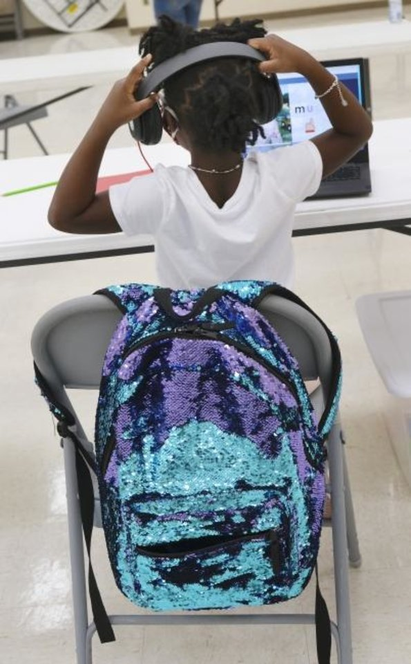 Photo -  Genesis adjusts her headphones while working on the computer on Monday, the opening day of the community hope center at Fifth Street Missionary Baptist Church. [Doug Hoke/The Oklahoman]