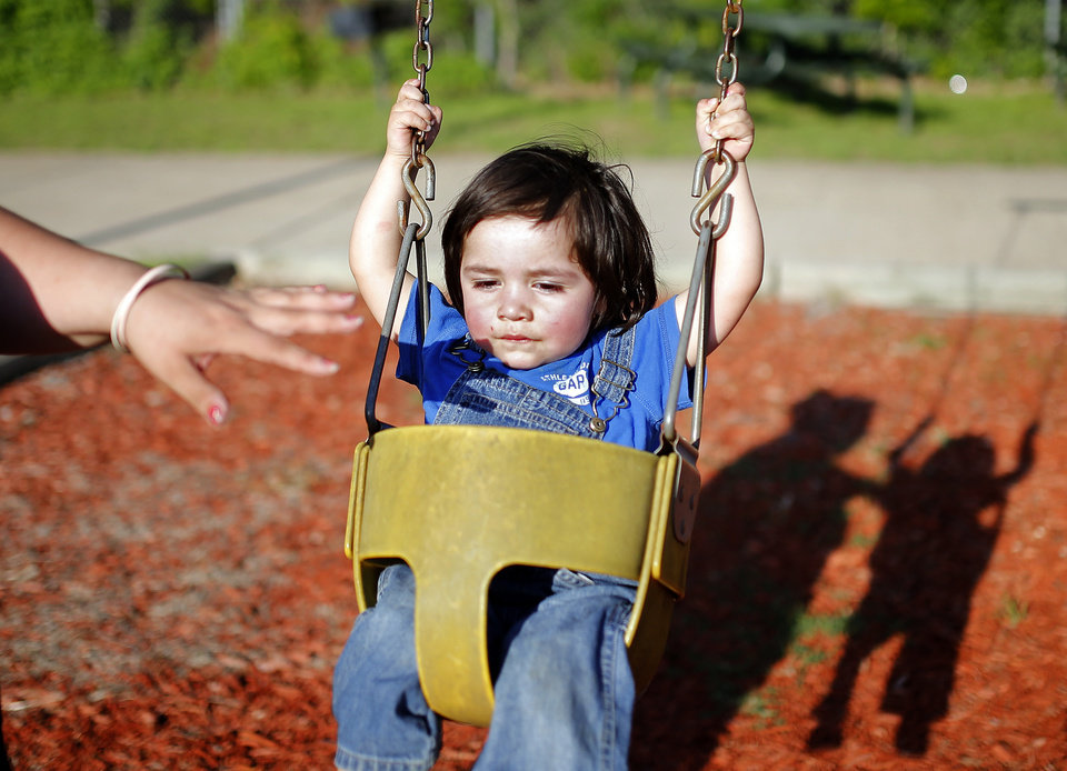 Photo - Talisa Doonkeen pushes her son, Conchattee, on a swing at the playground in their apartment complex.  Sarah PhIpps -  Sarah Phipps