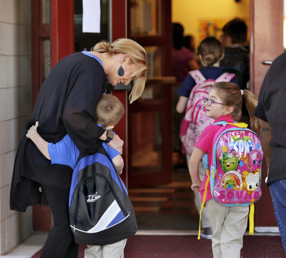 Photo - Principal Melissa Marschall hugs a boy as students enter the building on the first day of school at Cesar Chavez Elementary School on SE Grand Blvd. Students returned to classrooms across the city on Wednesday, Aug. 1, 2018, as Oklahoma City Public Schools started another school year. Photo by Jim Beckel, The Oklahoman