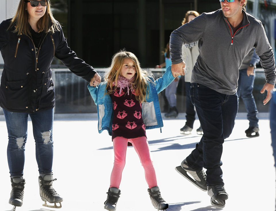 Photo -  Dominick Gobbo and Megan Hardy, from Chicago, support Hardy's niece, Adriana Hardy, 7, from Oklahoma City, as they show her how to skate Nov. 19 at the Devon Ice Rink in downtown Oklahoma City. [Photo by Jim Beckel, The Oklahoman]