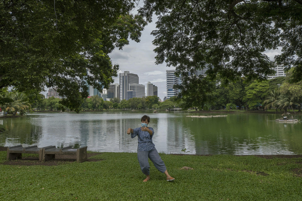 Photo -  A woman wearing a face mask to help curb the spread of the coronavirus practices Tai Chi at Lumpini park in Bangkok, Thailand, Friday, June 26, 2020. Daily life in the capital resumes to normal as the government continues to ease restrictions related to running business and activities that were imposed weeks ago to combat the spread of COVID-19. Thailand reported no local transmissions of the coronavirus in the past 4 weeks. (AP Photo/Sakchai Lalit)