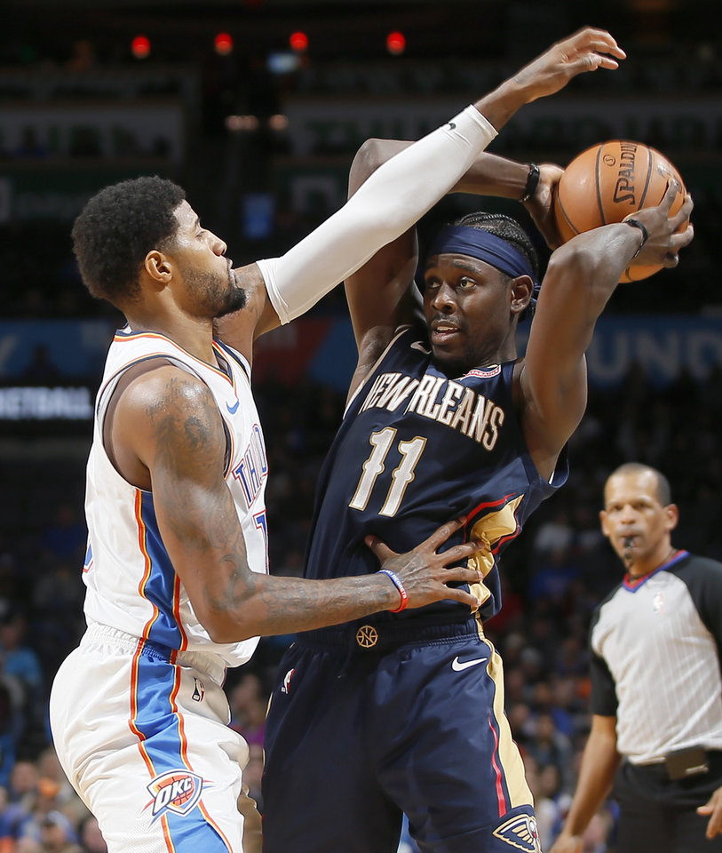 Photo - Oklahoma City's Paul George (13) defends New Orleans' Jrue Holiday (11) during an NBA basketball game between the Oklahoma City Thunder and the New Orleans Pelicans at Chesapeake Energy Arena in Oklahoma City, Thursday, Jan. 24, 2019. Photo by Bryan Terry, The Oklahoman