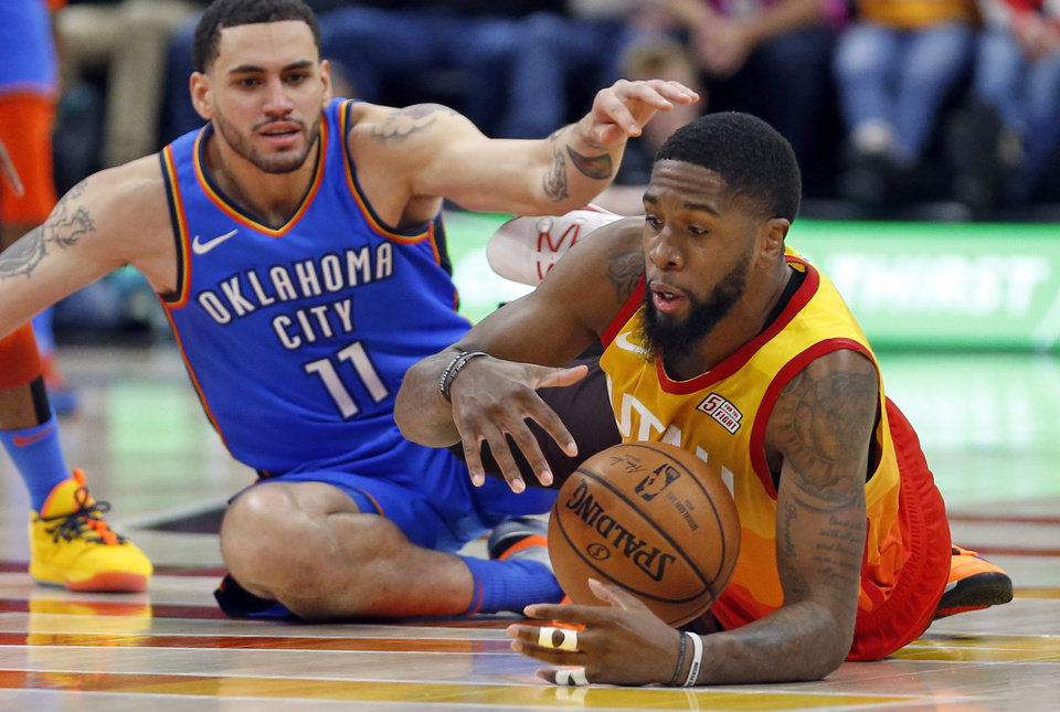 Photo - Utah Jazz forward Royce O'Neale, right, battles for the ball with Oklahoma City Thunder forward Abdel Nader (11) in the first half during an NBA basketball game Monday, March 11, 2019, in Kearns, Utah. (AP Photo/Rick Bowmer)
