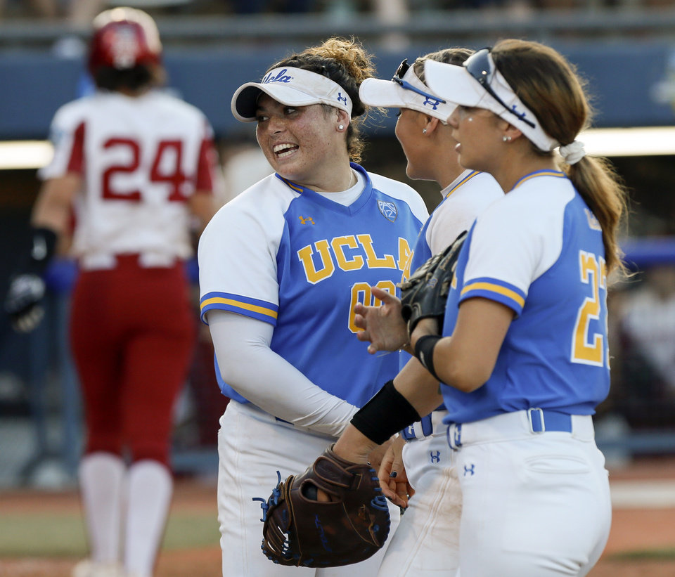 Photo - UCLA pitcher Rachel Garcia (00) smiles near teammates at the end of the fifth inning during the first NCAA softball game in the championship series of the Women's College World Series between Oklahoma and UCLA at USA Softball Hall of Fame Stadium in Oklahoma City, Monday, June 3, 2019. [Nate Billings/The Oklahoman]