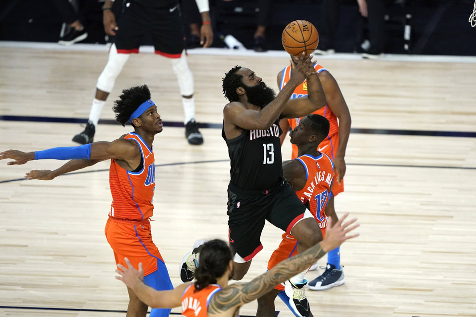 Photo - Houston Rockets' James Harden (13) goes up for a shot as Oklahoma City Thunder's Dennis Schroder (17) and Shai Gilgeous-Alexander, left, defend during the second half of an NBA basketball first round playoff game Saturday, Aug. 29, 2020, in Lake Buena Vista, Fla. (AP Photo/Ashley Landis)