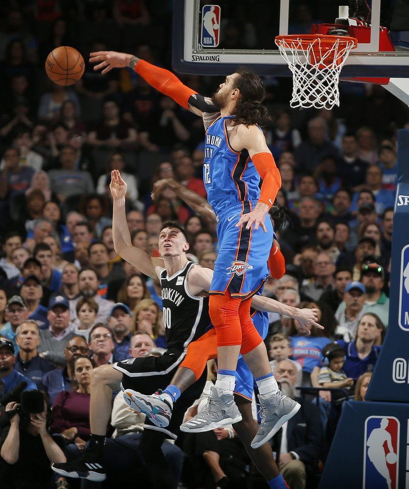 Photo - Oklahoma City's Steven Adams (12) defends Brooklyn's Rodions Kurucs (00) during an NBA basketball game between the Oklahoma City Thunder and the Brooklyn Nets at Chesapeake Energy Arena in Oklahoma City, Wednesday, March 13, 2019. Oklahoma City won 108-96. Photo by Bryan Terry, The Oklahoman