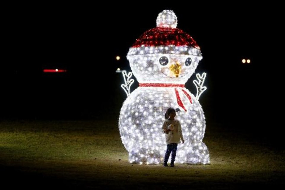 Photo -  People walk through Edmond Electric's Luminance holiday lights display at Mitch Park in Edmond. The free holiday light event will be featured from 5 to 10 nightly through Jan. 3. [Bryan Terry/The Oklahoman]