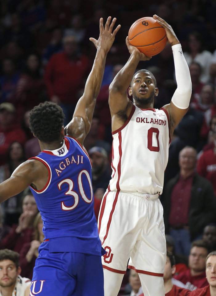 Photo - Oklahoma's Christian James (0) shoots over Kansas's Ochai Agbaji (30) during the men's college basketball game between the University of Oklahoma and Kansas at the Lloyd Noble Center in Norman, Okla., Tuesday, March 5, 2019. Photo by Sarah Phipps, The Oklahoman
