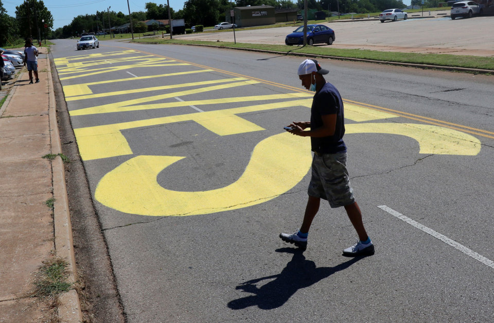 Photo - People come by to see and take photos and video of the Black Lives Matter! that was painted on the west bound lanes of Springlake Dr., just east of the intersection of NE 36th and Kelley Ave.,Wednesday, June 24, 2020. [Doug Hoke/The Oklahoman]