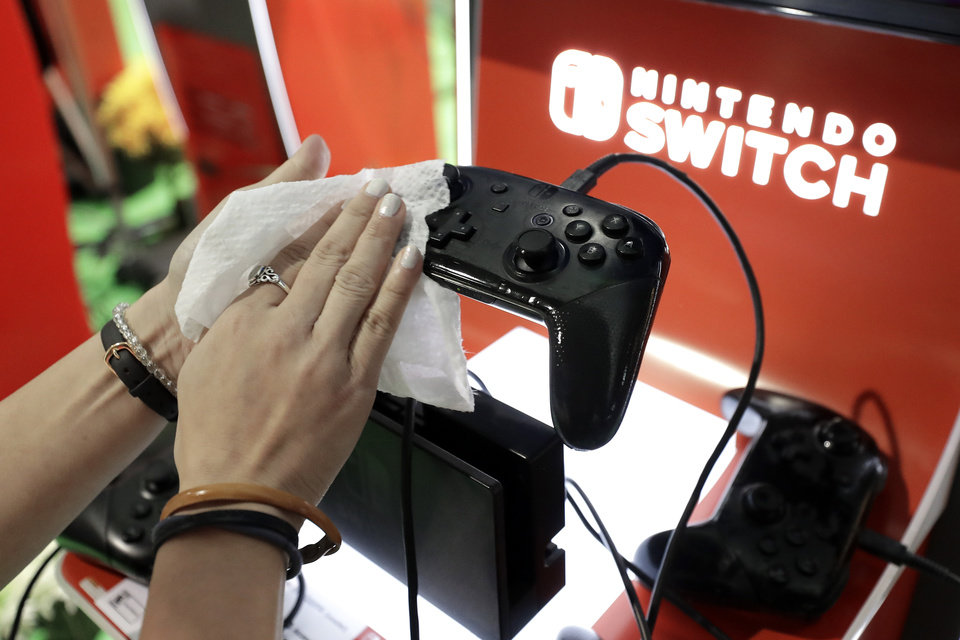 Photo -  FILE - In this Feb. 27, 2020, file photo, game demonstrator Alex Chang uses a disinfectant wipe to clean a game console at the Nintendo Switch exhibit at the Pax East conference in Boston.  Launched in 2017, the Switch became a fast seller. In March 2020, it became hard to find a Switch as people searched for ways to be entertained inside their homes. (AP Photo/Steven Senne, File)