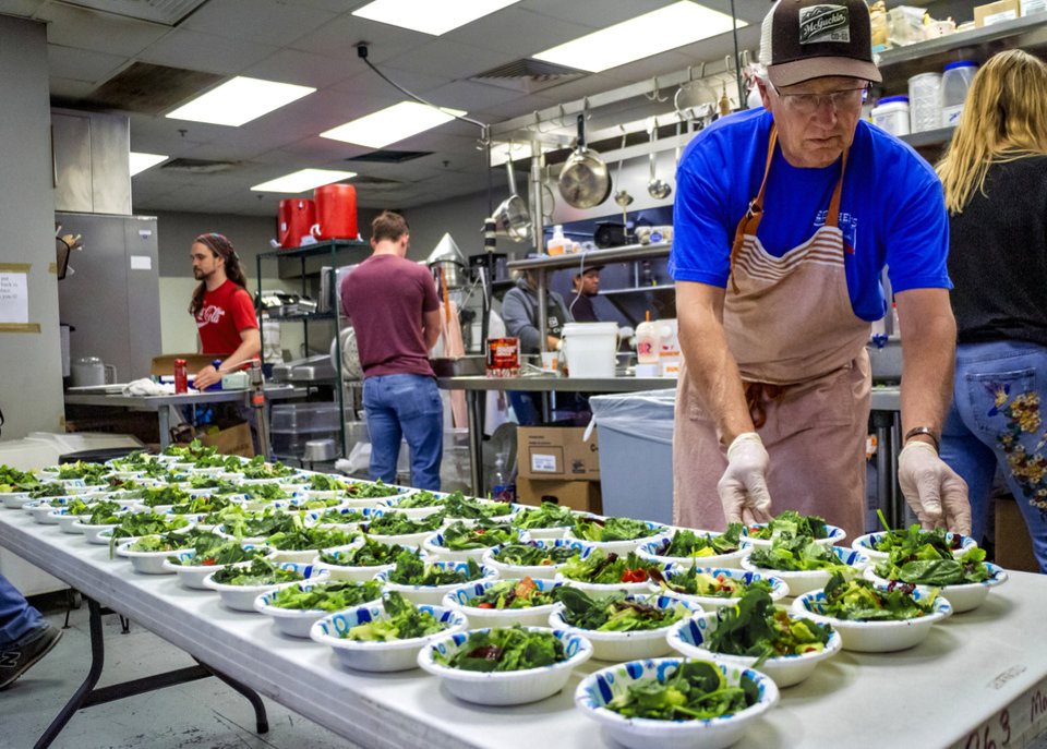 Photo - Bob Eskridge prepares food as 84 Hospitality works the kitchen of The Westtown day shelter at the Homeless Alliance to make lunch for the shelter's clients in Oklahoma City, Okla. on Monday, May 6, 2019.    [Chris Landsberger/The Oklahoman]