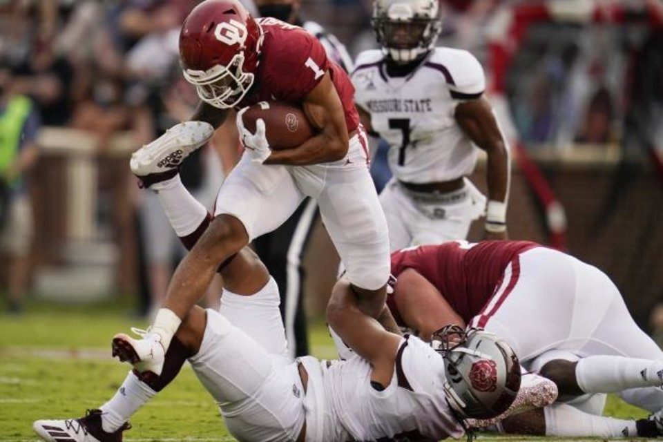 Photo -  Oklahoma running back Seth McGowan (1) fights off a tackle by Missouri State defender Ferrin Manulelua, bottom, in the first half of an NCAA college football game Saturday, Sept. 12, 2020, in Norman, Okla. (AP Photo/Sue Ogrocki, Pool)