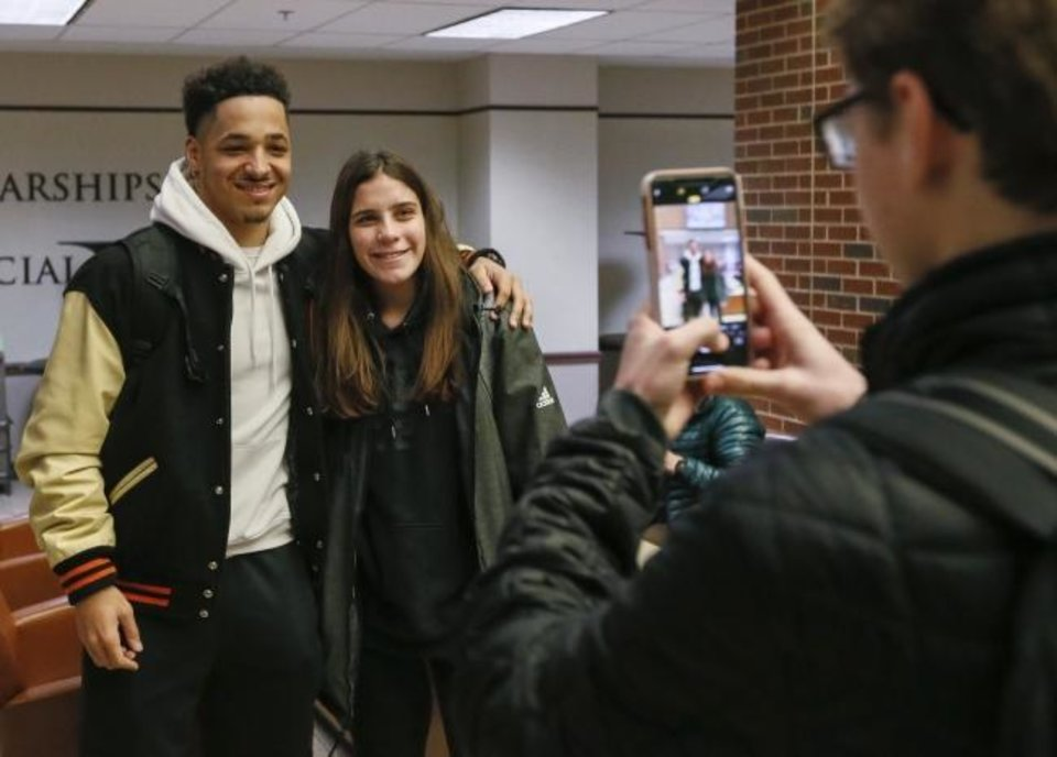 Photo -  Oklahoma State wide receiver Tylan Wallace, left, takes a photo with student Cassidy Breaux, 19, of Houston, after a football pep rally Tuesday in the Student Union. [Nate Billings/The Oklahoman]