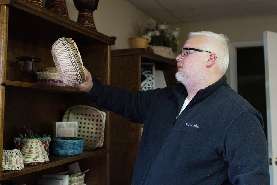 Photo -  Navy veteran Jeremy Housley looks at bowls that were woven by clients at Norman's Transition House where Housley is receiving mental health treatment and temporary shelter. [PHOTO BY WHITNEY BRYEN FOR THE OKLAHOMAN]