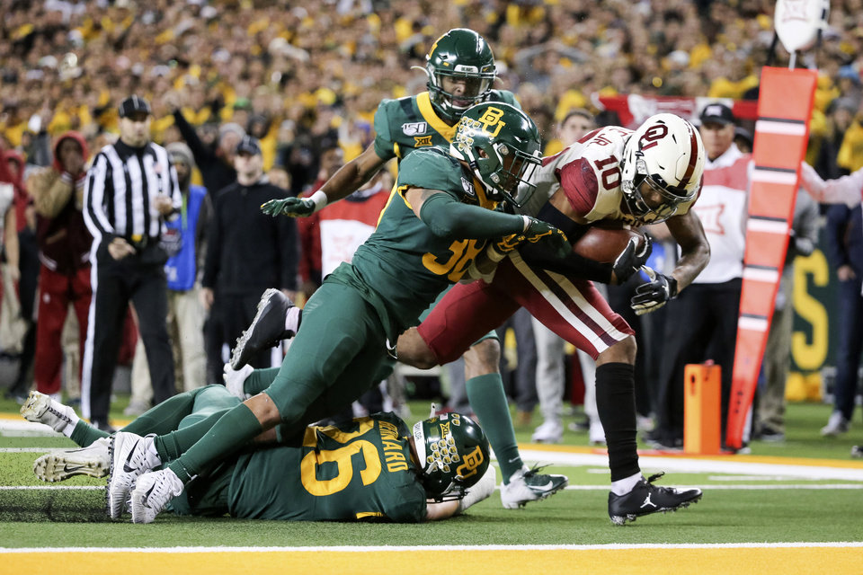 Photo - Oklahoma wide receiver Theo Wease (10) scores a 19-yard touchdown as Baylor linebacker Jordan Williams (38) defends during the second half of an NCAA college football game in Waco, Texas, Saturday, Nov. 16, 2019. Oklahoma won 34-31. (AP Photo/Ray Carlin)