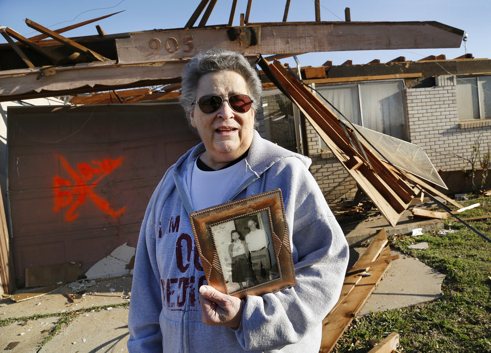 Photo - Joetta Strain shares her joy after her grandson went inside her badly damaged home at 905 NW 2 and came back out with this framed photo of Strain's mother and father. She said finding the photo of her parents was reason to celebrate. Strain has a storm shelter in her backyard but she didn't have time to get in it so she squeezed into a hall closet as the twister passed over and ripped away the roof of her 3 bedroom home. She has lived in the home since 1973. She was not injured in the tornado.  Her block is between NW 5 and Main Street, and between Telephone Rd. and Santa Fe in Moore. She is photographed on Thursday morning, March 26, 2015, the day after a tornado damaged homes and a school the previous night. Photo by Jim Beckel, The Oklahoman