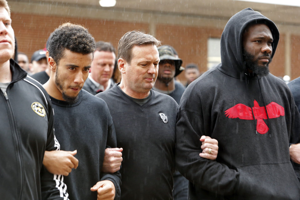 Photo - University of Oklahoma Sooner (OU) football players march arm in arm to the Everest Center dressed in black and cancel their scheduled practice on March 9, 2015 in Norman, Okla.  The gesture was apparently in response to the day's events surrounding racist comments made by an OU fraternity.   Photo by Steve Sisney, The Oklahoman