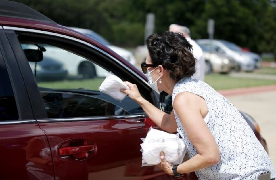 Photo -  Village City Councilwoman Cathy Cummings hands out a pack of masks during a drive-thru mask giveaway event at Chabad Community Center for Jewish Life and Learning, 3000 W Hefner Road.   [Sarah Phipps/The Oklahoman]