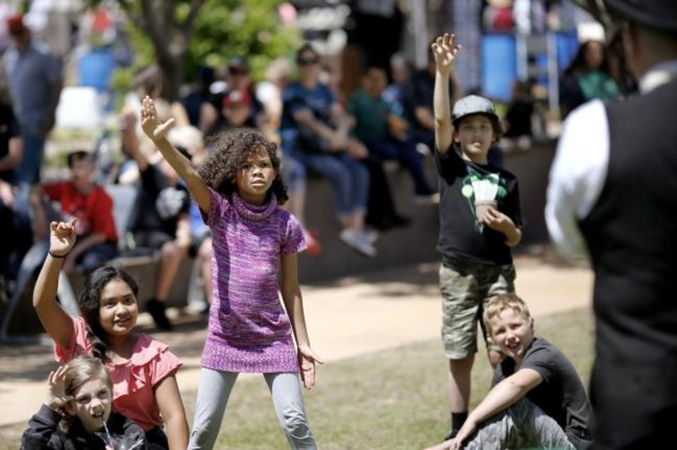 Photo -  Jordin Peavler, 9, of Norman, center, responds to Capstone the Magician, the street performer at this year's Festival of the Arts, during a Thursday afternoon performance at the downtown Oklahoma City event. He is performing 40-minute sets at at noon, 2:30 and 7:45 p.m. Friday and Saturday; and at noon, 2 and 4 p.m. Sunday. Performances are on the Colcord Lawn at Bicentennial Park, near the Civic Center. [Jim Beckel/The Oklahoman]