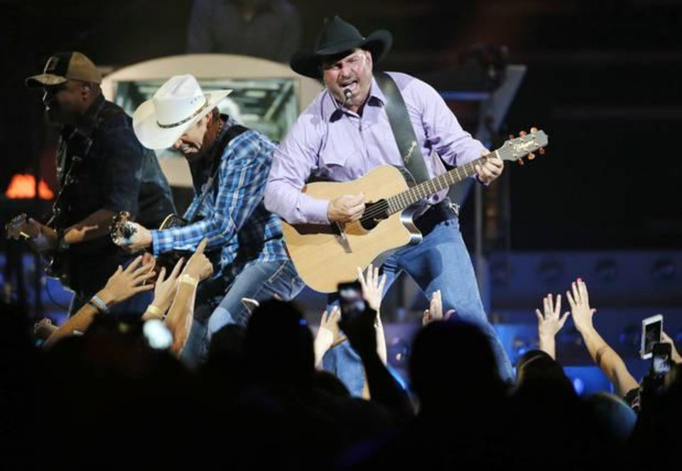 Photo - Garth Brooks, right, performs with his band during his 7 p.m. show at the Chesapeake Energy Arena in Oklahoma City, Friday, July 14, 2017. Photo by Nate Billings, The Oklahoman Archives
