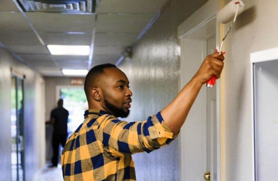 Photo -  Experts say those who help others were most likely to thrive.  Kyree Williams applies a new coat of paint to the walls in 2018 during the United Way Day of Caring at HeartLine Inc. in Oklahoma City. [Chris Landsberger, The Oklahoman Archive]