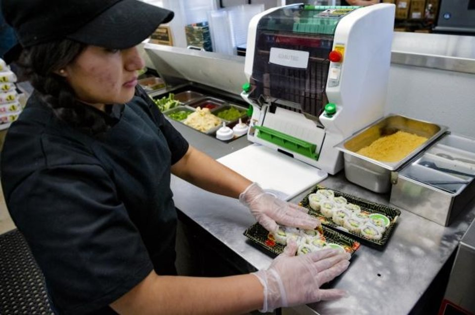 Photo -  Employee Julie Lopez arranges a plate of sushi after using the new automated Sushi Cutter, shown at left.  [Chris Landsberger/The Oklahoman]