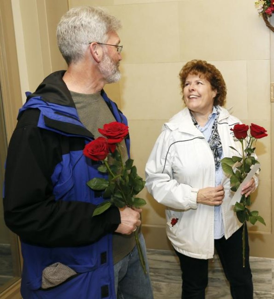 Photo -  Tim Taylor and Ann Taylor, of Hennessey, chat Wednesday after leaving roses in the office of Sen. Chuck Hall during Rose Day at the state Capitol. [Nate Billings/The Oklahoman]