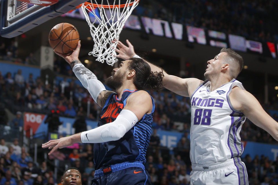 Photo - Oklahoma City's Steven Adams (12) goes ast Sacramento's Nemanja Bjelica (88) during an NBA basketball game between the Oklahoma City Thunder and the Sacramento Kings at Chesapeake Energy Arena in Oklahoma City, Sunday, Oct. 21, 2018. Photo by Bryan Terry, The Oklahoman